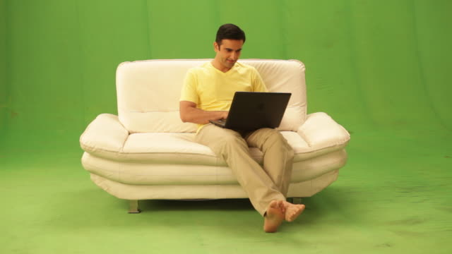 man shopping from a laptop through a credit card  - sofa stock videos & royalty-free footage