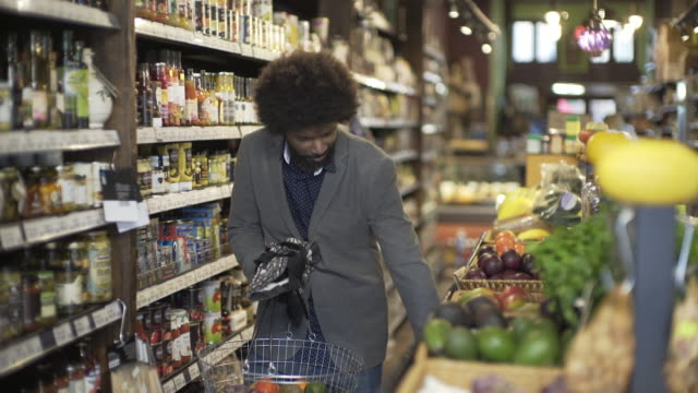 a man shopping in a local organic grocery store. - health food shop stock videos and b-roll footage