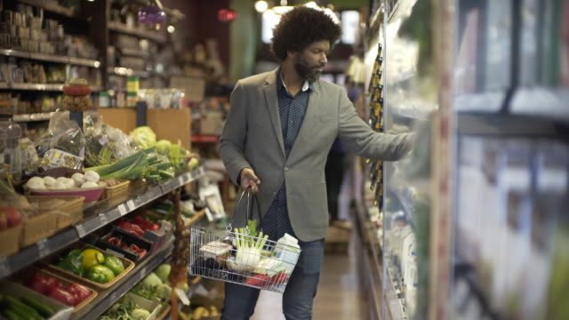 a man shopping in a local organic grocery store. - shopping basket stock videos and b-roll footage