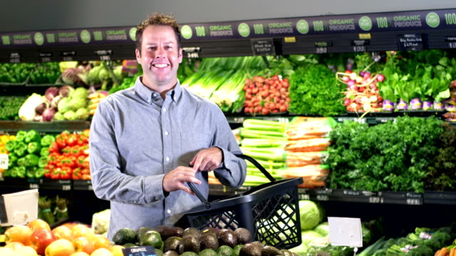 man shopping in produce aisle at supermarket - shopping basket stock videos and b-roll footage
