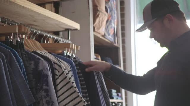 vídeos y material grabado en eventos de stock de man shops for shirts in high end clothing store. - gorra de béisbol