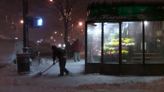 a man shoveling a street corner at night outside of a flower shop. - fioraio negozio video stock e b–roll