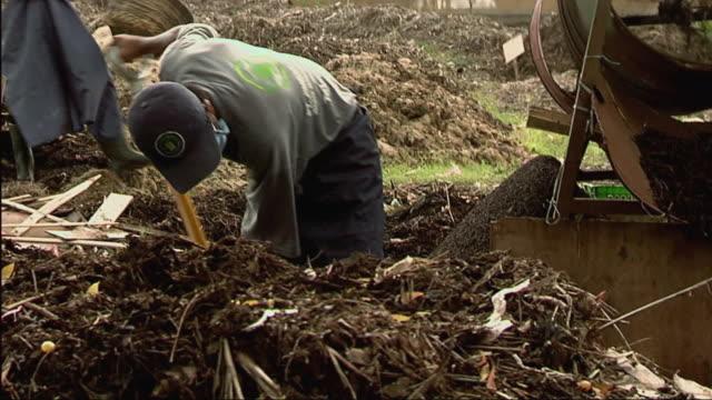 cu zo zi man shoveling dirt into composting machine / bali, indonesia - machinery stock videos & royalty-free footage