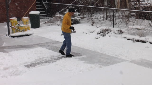 WS ZI Man shoveling snow from sidewalk / Chicago, Illinois, USA