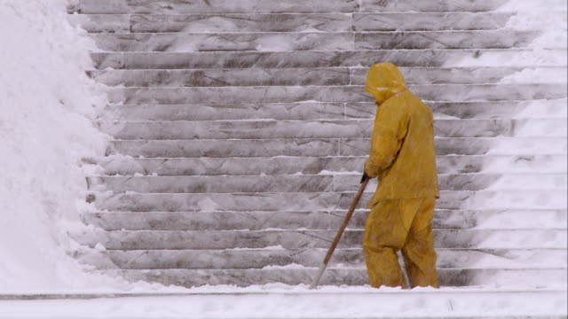 vídeos de stock e filmes b-roll de man shoveling snow in central park during a snowstorm - pá para neve