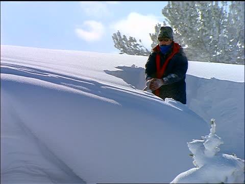 vídeos de stock e filmes b-roll de man shoveling snow in tall snowbank - pá para neve