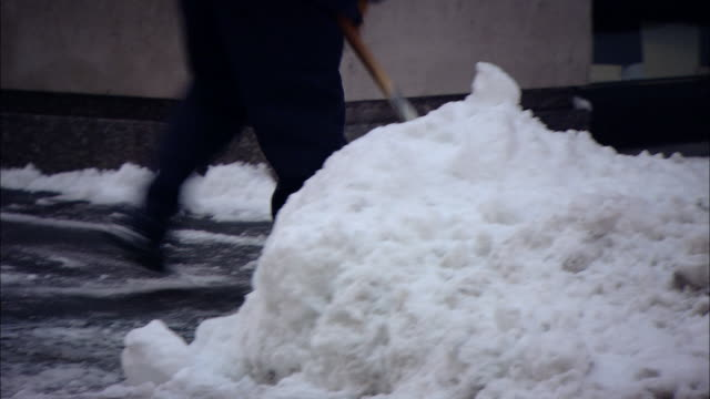 vídeos de stock e filmes b-roll de ms pan zo man shoveling snow to clear sidewalk in front of store in shopping area and  people walking to work / new york, new york, united states - pá para neve