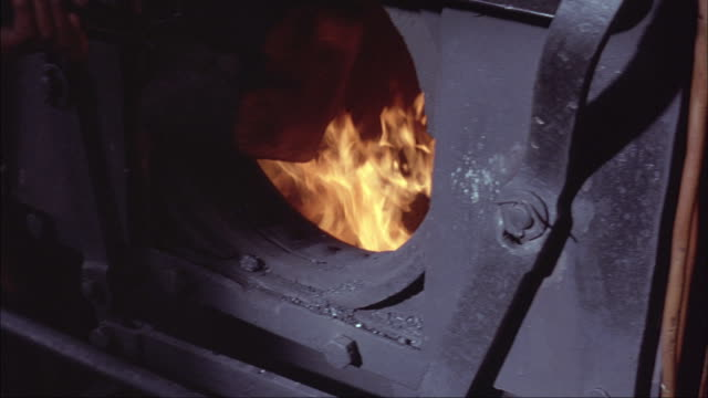 a man shovels coal into a burning furnace. - burning stock videos & royalty-free footage