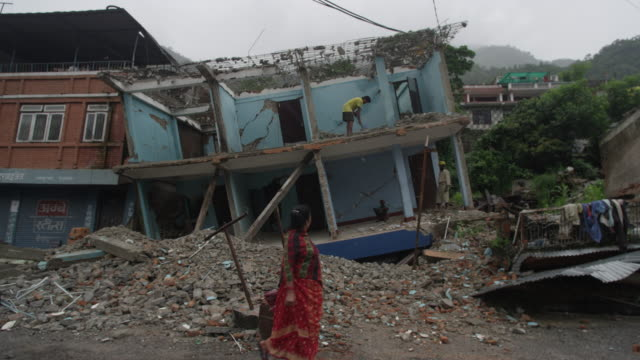 barabise, nepal - july 31, 2015: man shovels rubble from destroyed house, passersby - 自然災害点の映像素材/bロール