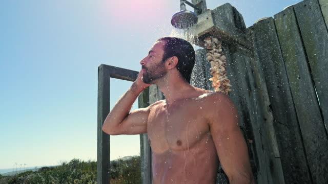 vídeos de stock e filmes b-roll de man showering - homem tomando banho