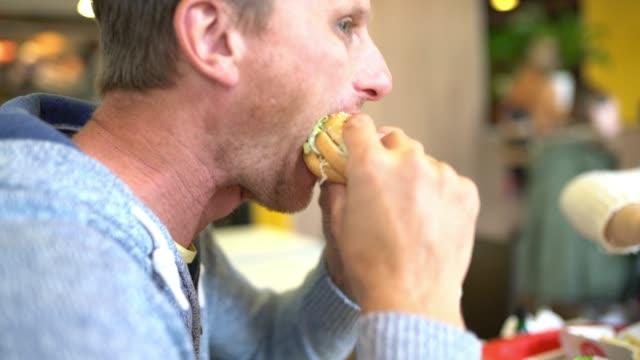 ms man showing a thumb up while eating a hamburger - hamburger stock videos & royalty-free footage