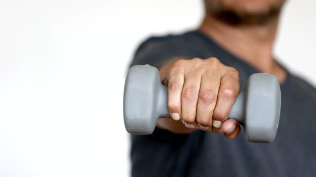 vídeos de stock e filmes b-roll de man showing exercise equipment - weightlifting dumbbell - flexão de braço com peso