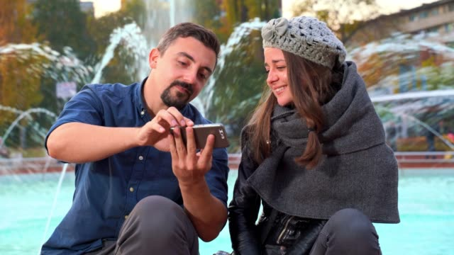Man showing girl something on his smart phone outdoors