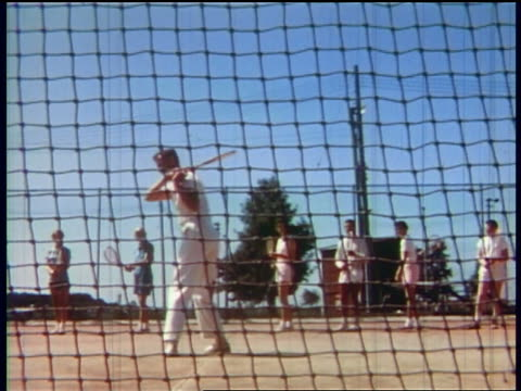 1957 man showing group of people how to swing tennis racquet / educational - 1957 stock-videos und b-roll-filmmaterial