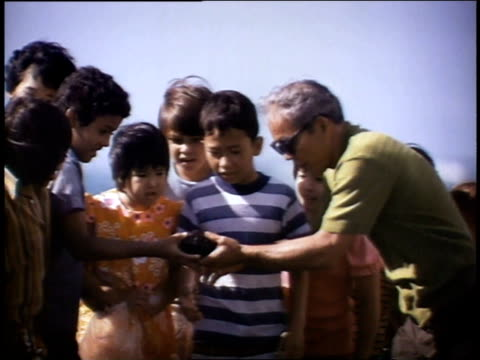 1975 MS Man showing sea urchin to children / United States