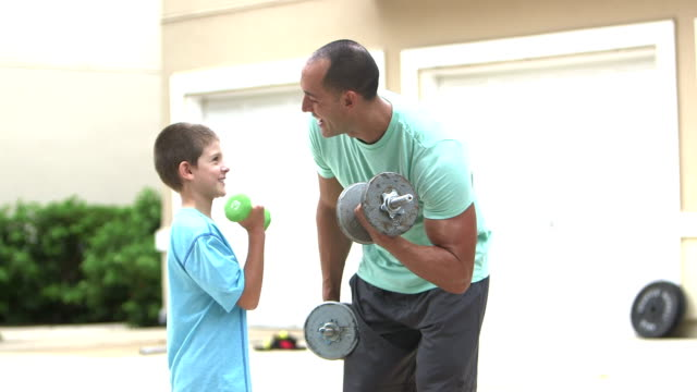 man showing son how to lift weights - native american ethnicity stock videos and b-roll footage