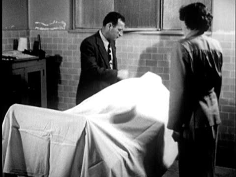 1955 B/W LS Man showing woman body in morgue lifting sheet revealing head of body / United States / AUDIO