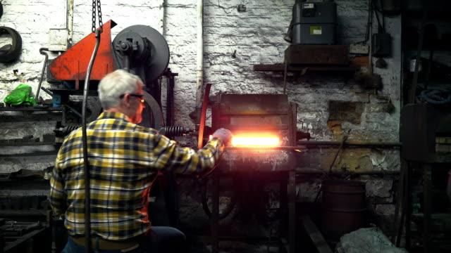 vídeos y material grabado en eventos de stock de man showing woman metal from furnace - cabello canoso