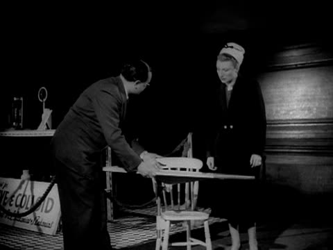 a man shows a woman an ironing board that can be attached to a chair at an inventions exhibition - bügelbrett stock-videos und b-roll-filmmaterial
