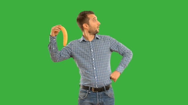 man shows copy space and smiling on a green background