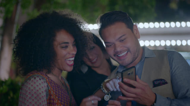 man shows friends pictures on smartphone on night out in las vegas. - oggetto creato dall'uomo video stock e b–roll