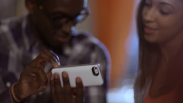 Man shows off smartphone features to woman at dinner table