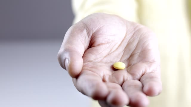 man shows one yellow pill to the camera - anti impotence tablet stock videos & royalty-free footage