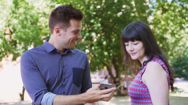 vídeos de stock e filmes b-roll de man shows woman something on his phone - mostrar