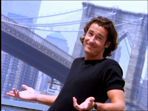 man shrugging + smiling at camera / brooklyn bridge + nyc skyline in background - 1997 stock videos & royalty-free footage