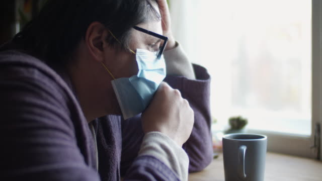 man sick at home wearing protective mask and coughing - symptom stock videos & royalty-free footage