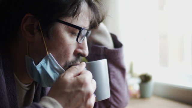man sick at home wearing protective mask and drinking tea - cup stock videos & royalty-free footage