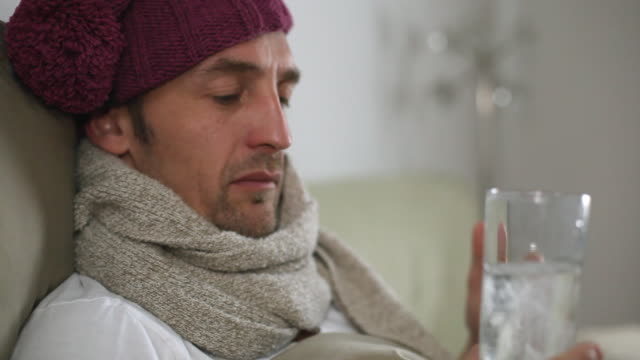 cu man sick in bed, dissolving an effervescent tablet in glass of water / potsdam, brandenburg, germany - auflösen stock-videos und b-roll-filmmaterial