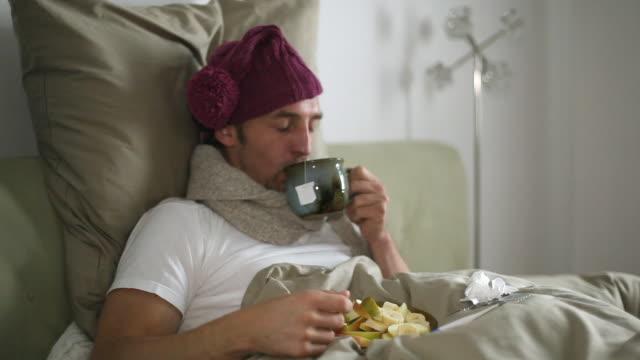 ms man sick in bed drinking tea / potsdam, brandenburg, germany - krankheit stock-videos und b-roll-filmmaterial