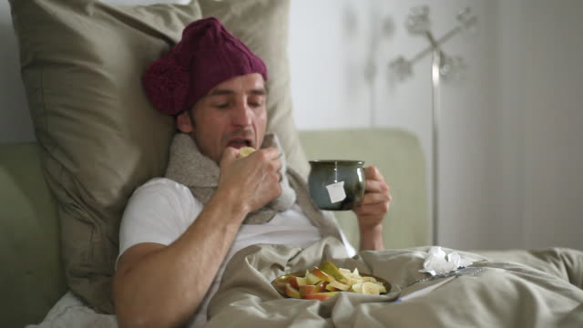 MS Man sick in bed, eating fruits and drinking tea / Potsdam, Brandenburg, Germany