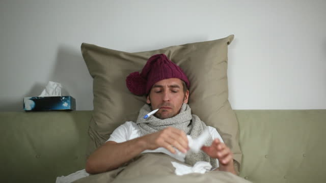 vídeos de stock, filmes e b-roll de ms man sick in bed putting thermometer in mouth / potsdam, brandenburg, germany - febre