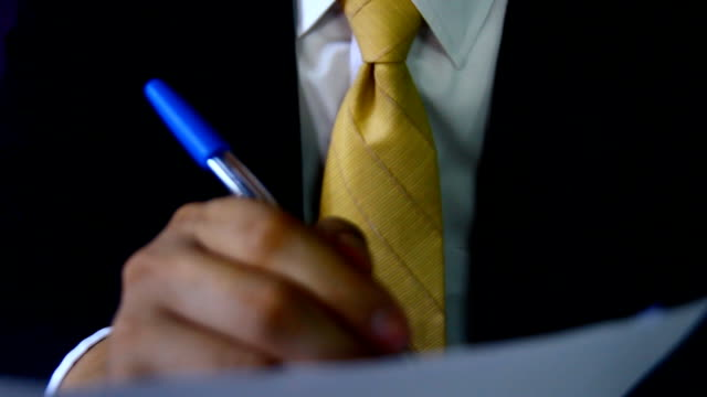 Man signing a document or writing correspondence with a close up view of his hand with the pen and sheet of notepaper on a desk top.