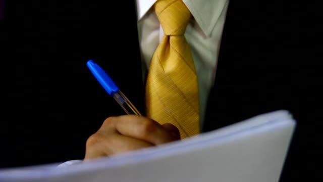 vidéos et rushes de homme signature sur un document ou écrire des lettres avec un gros plan sur la main avec le stylo et une feuille de papier à lettres sur un bureau-dessus. - lettre document
