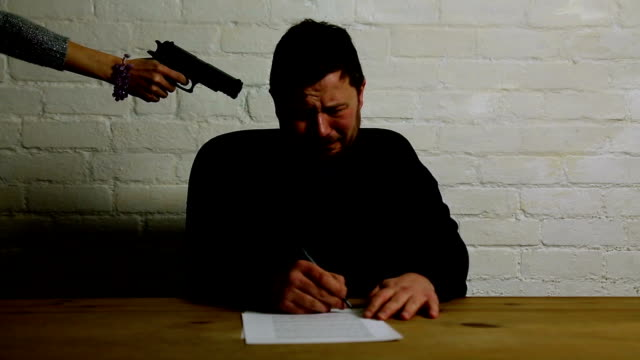 man signing contract at womans gun point under threat - 脅し点の映像素材/bロール