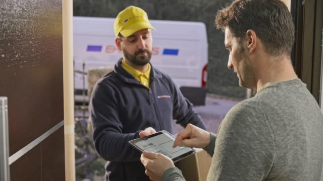 man signing for the package being delivered to his front door by a male courier - doorway stock videos & royalty-free footage