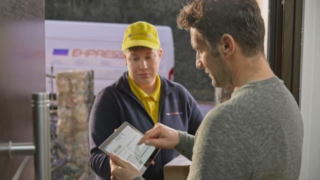 笑顔の女性宅配便によって彼の玄関に配達されているパッケージに署名する男 - 受ける点の映像素材/bロール