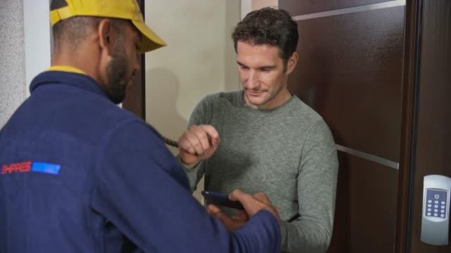 vidéos et rushes de l'homme signant le pod numérique avant que le messager masculin lui remet le paquet à la porte d'entrée - deux personnes
