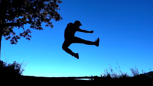 slo mo man silhouette jumping and kicking with blue sky - kicking stock videos & royalty-free footage