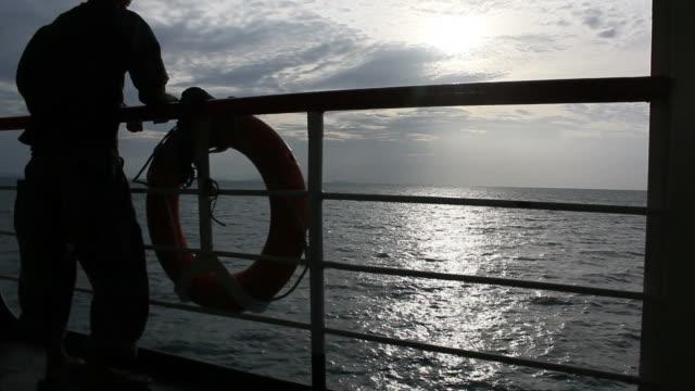 vídeos de stock e filmes b-roll de silhueta de homem no barco - navio de passageiros