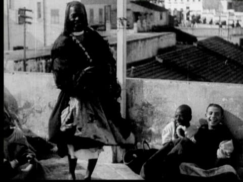 1934 b/w montage ms cu ws man singing, dancing and playing finger cymbals with three boys looking and laughing, group of men wearing traditional robes dancing in a circle, city view through arched gate / rabat, morocco - braided hair stock videos & royalty-free footage