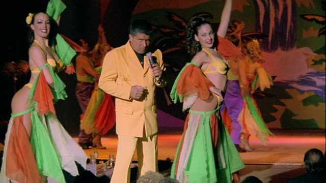 ms man singing on stage with dancers in costume behind him - showgirl stock videos and b-roll footage