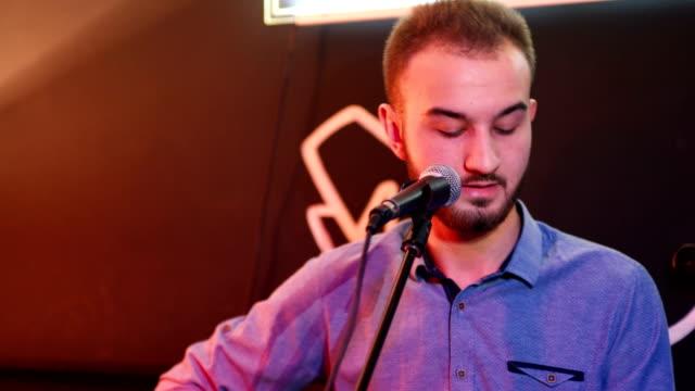 男が歌うし、アコースティック ギターを果たしています。 - シンガーソングライター点の映像素材/bロール