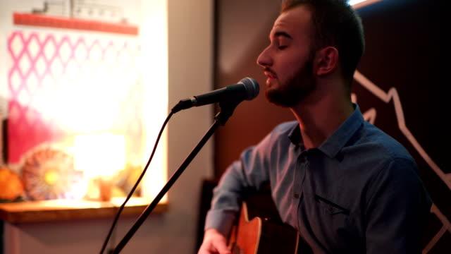 男が歌うとアコースティックギターを演奏 - シンガーソングライター点の映像素材/bロール