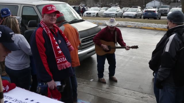 a man sings to people waiting in line and a vendor sells trump merchandise as people wait to see republican presidential candidate donald trump speak... - vorwahl stock-videos und b-roll-filmmaterial