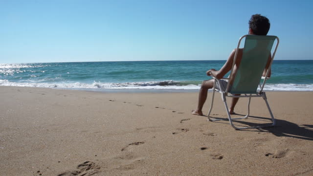 vidéos et rushes de man sit in a chair delightful beach with nobody - bain de soleil