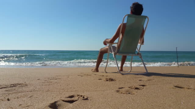 man sit in a chair delightful beach with nobody - water's edge stock videos & royalty-free footage